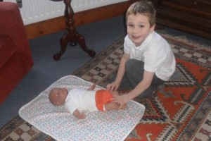 Big Brother Sam practising nappy changing